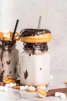 Вид спереди десертов в банках с кренделями и пончиками
