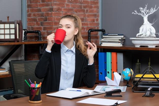 책상에 앉아 사무실에서 뭔가를 마시는 단호한 젊은 여성의 전면 보기