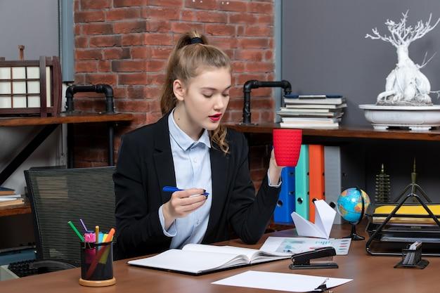 책상에 앉아 사무실에 빨간 컵 파란색 펜을 들고 있는 단호한 젊은 여성의 전면 모습