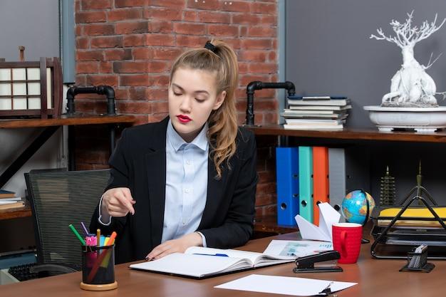 책상에 앉아 사무실에 있는 문서의 한 지점을 가리키는 단호한 젊은 여성의 전면