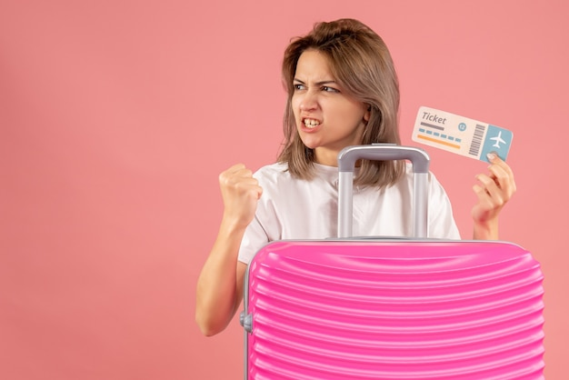 チケットを保持しているピンクのスーツケースを持つ決意の少女の正面図