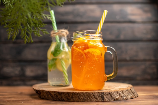 茶色の木製の背景にチューブが付いているボトルのデトックス水とフレッシュ ジュースの正面図