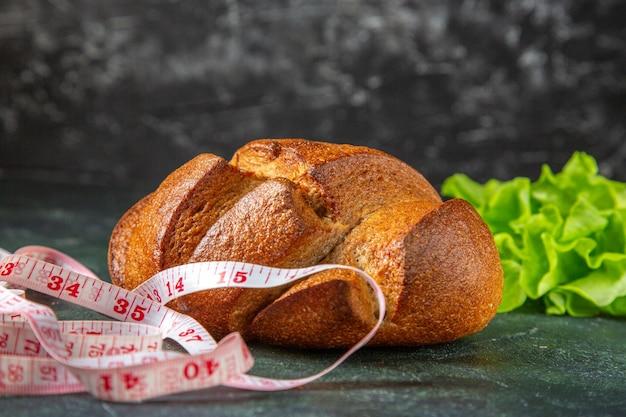 暗い色の表面の食餌療法の黒いパンとメートルの緑の束の正面図