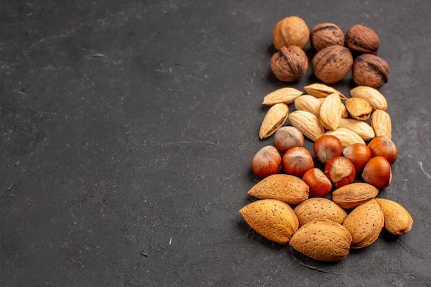 暗い表面のさまざまな新鮮なナッツの正面図