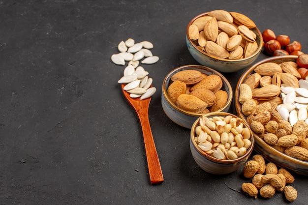 暗い表面の鉢の中のさまざまなナッツの新鮮なナッツの正面図