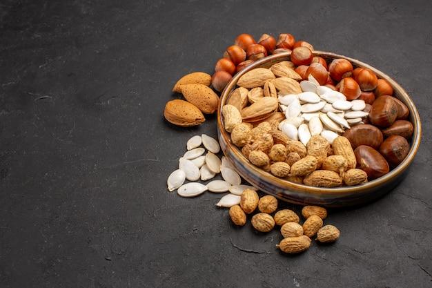 暗い表面のトレイ内のさまざまなナッツの新鮮なナッツの正面図