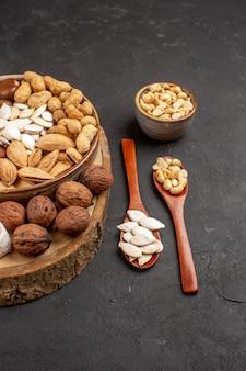 ダークグレーの表面にあるさまざまなナッツの新鮮なナッツの正面図