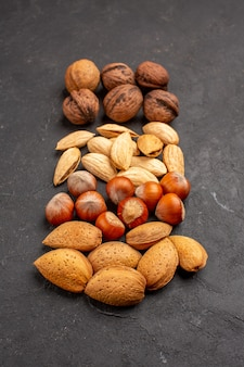 灰色の表面のさまざまなナッツの新鮮なナッツの正面図