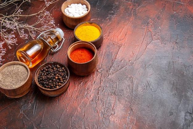 暗い表面に油を塗ったさまざまな調味料の正面図