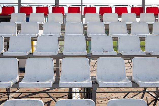 Вид спереди грязных белых и красных пластиковых сидений на трибуне стадиона