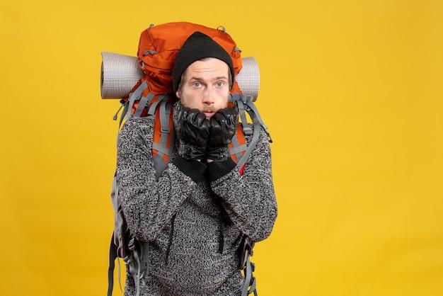 Вид спереди разочарованного автостопщика-мужчины с кожаными перчатками и рюкзаком