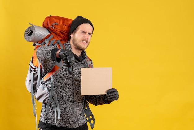 Вид спереди недовольного автостопщика-мужчины с кожаными перчатками и рюкзаком, держащего пустой картон, жестикулирующий пальцем вниз