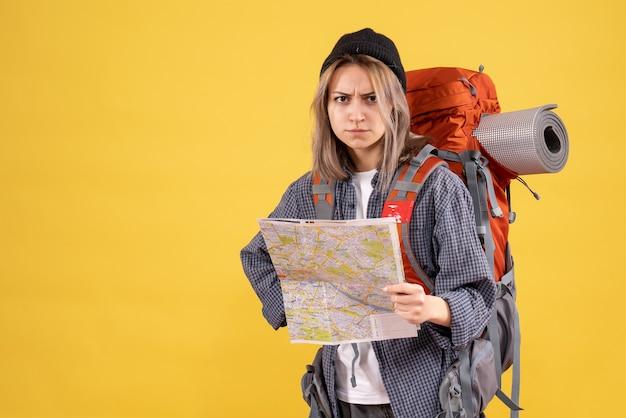 Вид спереди недовольной путешественницы с рюкзаком, держащей карту, смотрящую вперед