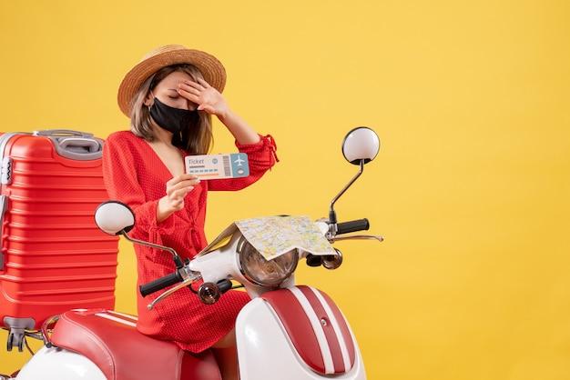 티켓을 들고 빨간 가방으로 오토바이에 불만족 된 젊은 아가씨의 전면보기