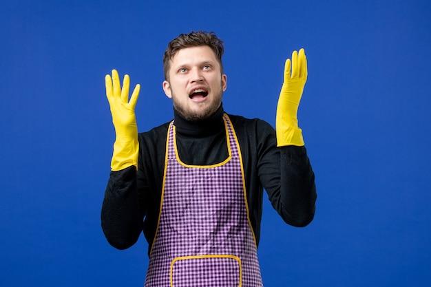 파란색 벽에 서 있는 불만족한 젊은 남성의 손을 벌리는 전면 모습