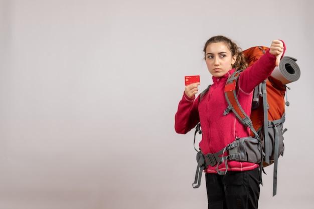 Вид спереди недовольного молодого путешественника с большим рюкзаком, держащего карточку, делающую большой палец вниз знак
