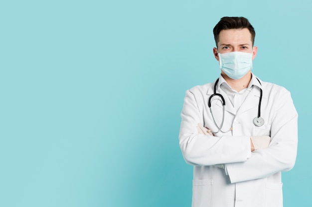 Вид спереди доктора с медицинской маской, позирует со скрещенными руками