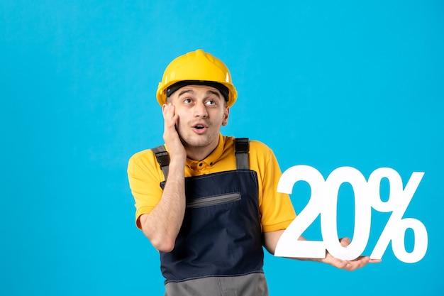 파란색 표면에 제복을 입은 꿈꾸는 남성 노동자의 전면보기