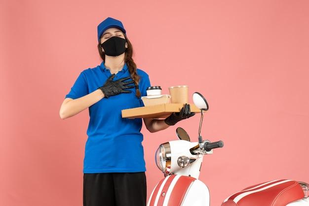 パステル ピーチ色の背景にコーヒーの小さなケーキを保持しているオートバイの隣に立っている医療マスク手袋を着た夢のような宅配便の女の子の正面図