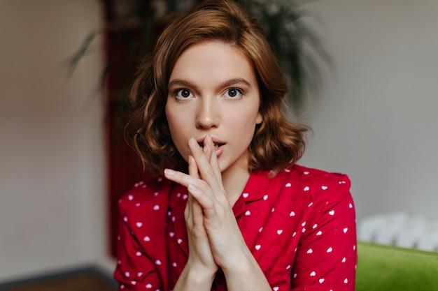 カメラを見ている夢のような巻き毛の女性の正面図。赤いパジャマを着た見事な白人女性の屋内ショット。
