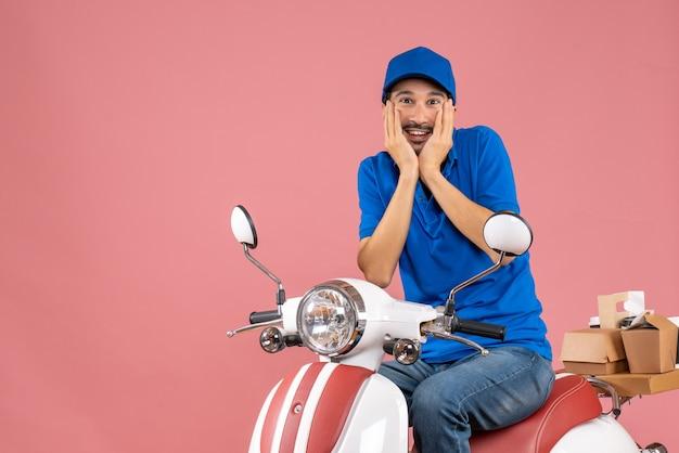 Вид спереди мечтательного курьера в шляпе, сидящего на скутере на пастельном персиковом фоне