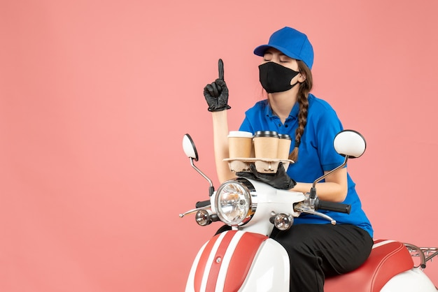 パステル調の桃の背景に注文を保持しているスクーターに座っている医療用マスクと手袋を着た夢のような女性配達員の正面図