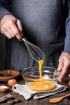 Вид спереди яиц в миске на деревянном столе