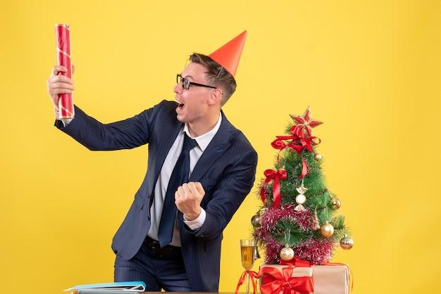 クリスマスツリーの近くのテーブルの後ろに立って、黄色でプレゼントパーティーポッパーを保持している大喜びのビジネスマンの正面図