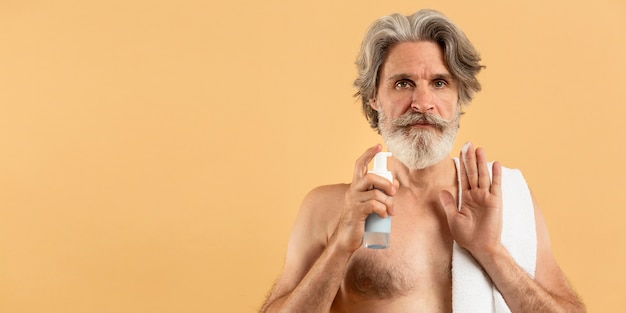 コピースペースと洗剤を保持している高齢者のひげを生やした男の正面図