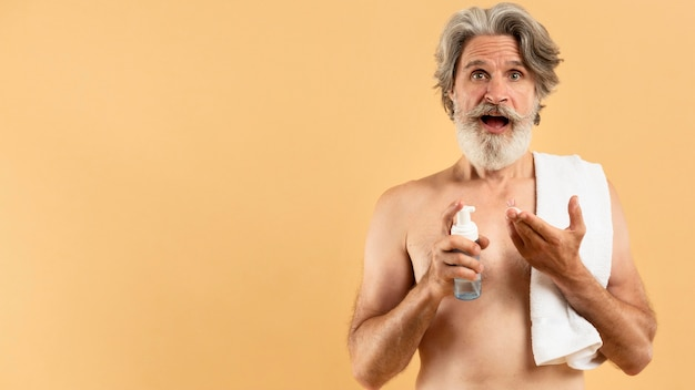 クレンザーを保持している高齢者のひげを生やした男の正面図