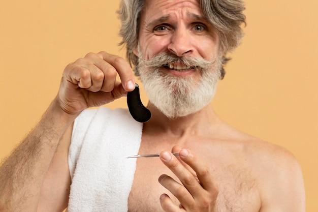 Вид спереди старшего бородатого мужчины, держащего глазные пятна