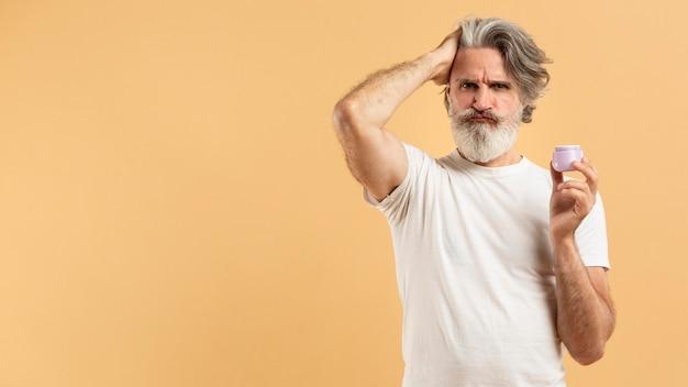 コピースペースを持つヘアジェルを保持している高齢者のひげを生やした男の正面図
