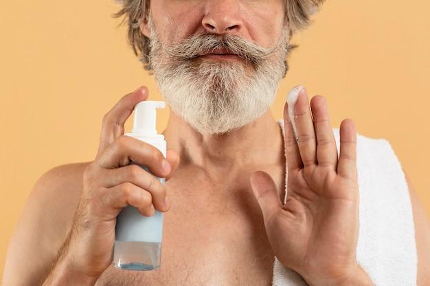 クレンザーを使用して高齢者のひげを生やした男の正面図