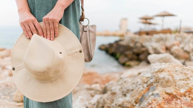 Вид спереди старшей туристической женщины, держащей шляпу