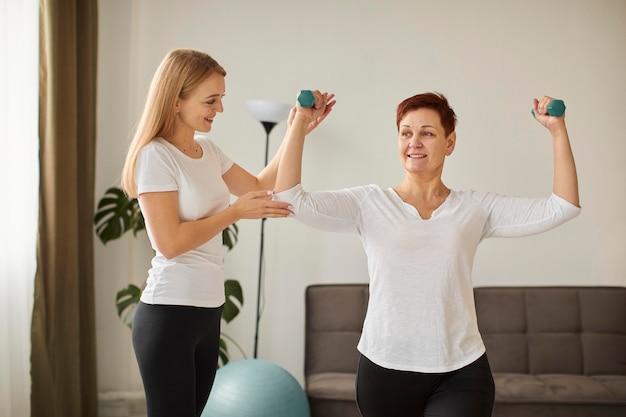 아령으로 운동을하는 covid 회복에 노인 여성의 전면보기