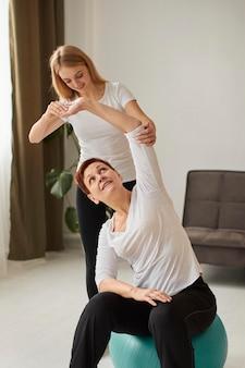 간호사와 함께 운동을하는 covid 회복에 노인 여성의 전면보기