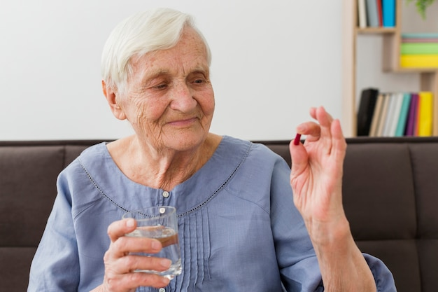 Вид спереди пожилой женщины, принимая ее ежедневные таблетки