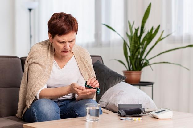 Вид спереди старшей женщины, принимающей таблетки для ее состояния