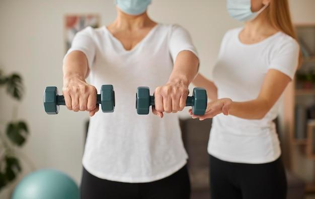 아령으로 운동을하는 covid 회복에 의료 마스크와 노인 여성의 전면보기