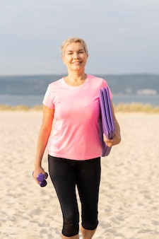 ビーチで機器をトレーニングしている年配の女性の正面図