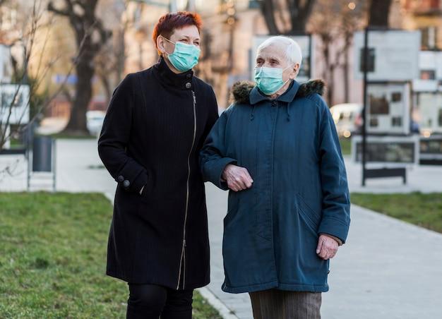 医療マスクを身に着けている都市の高齢者の女性の正面図