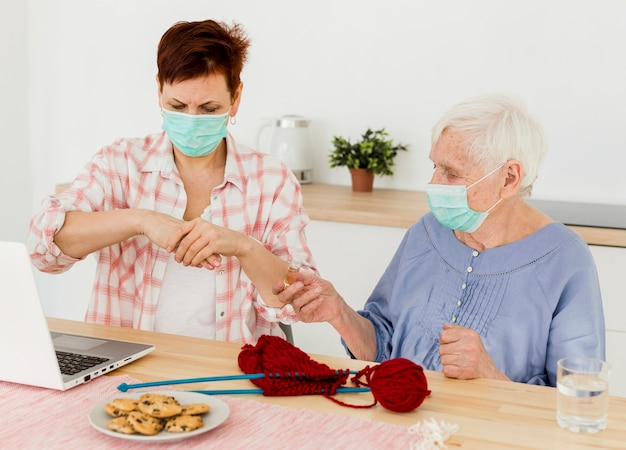 高齢者の女性が自宅で手を消毒するの正面図