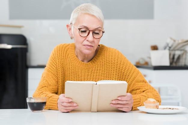 Вид спереди пожилой женщины, читающей книгу