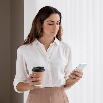 Вид спереди элегантной деловой женщины, держащей чашку кофе и смартфон