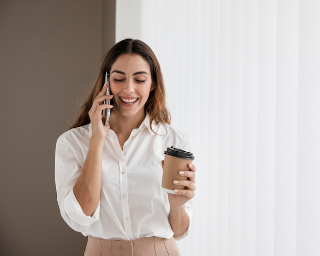 Вид спереди элегантной деловой женщины разговаривает по телефону, держа чашку кофе