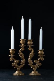 Вид спереди элегантного подсвечника со свечами на темной поверхности