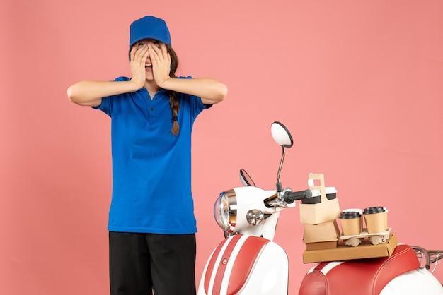 Вид спереди эмоциональной курьерской дамы, стоящей рядом с мотоциклом с кофе и небольшими пирожными на нем на фоне пастельного персикового цвета