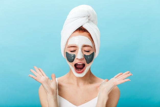 스킨 케어 치료를하는 동안 비명을 지르는 감정적 인 소녀의 전면 모습. 파란색 배경에 고립 된 얼굴 마스크와 놀라운 아가씨의 스튜디오 샷.