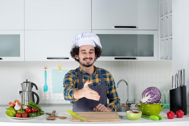 新鮮な野菜とキッチンツールで調理し、白いキッチンで誰かを歓迎する感情的な男性シェフの正面図