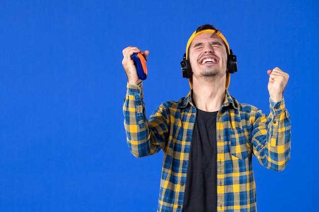 파란색 벽에서 비디오 게임을 하는 게임패드가 있는 감정적인 남성 게이머의 전면